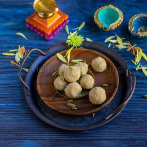 square image of thinai laddu placed on a wooden plate with lamp lit on the side