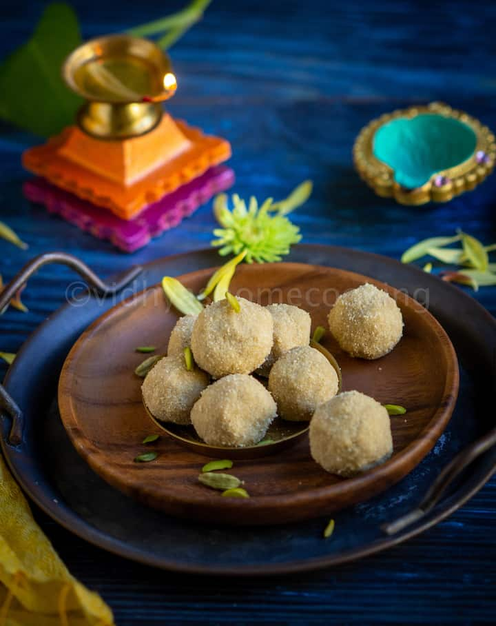 thinai laddu served on a wooden plate with flowers and nuts drizzled with lamps on the side