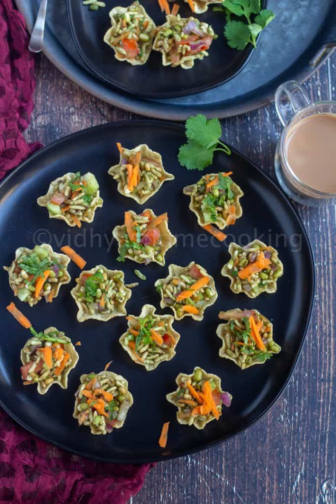 tortilla bhel cups placed on a black plate with tea on the side