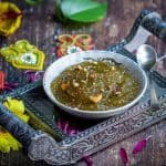 square image of zucchini halwa served on a bowl placed on a silver tray