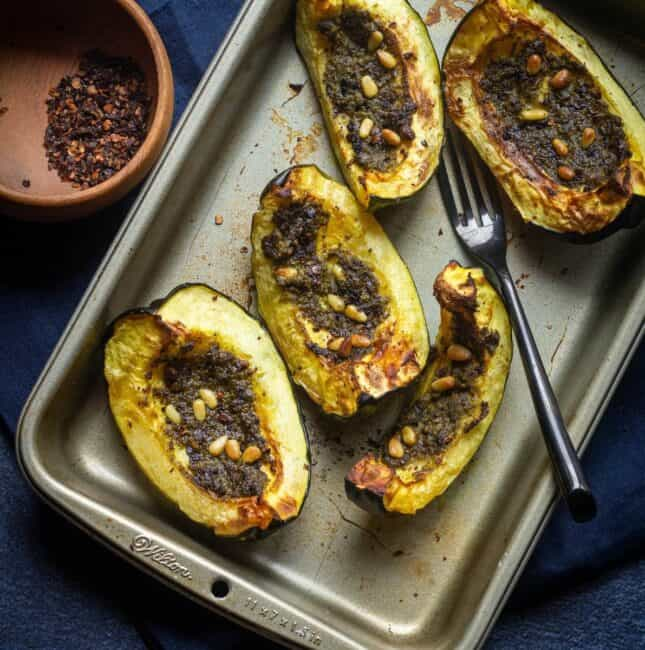 roasted acorn squash placed on a baking tray with chipotle chili flakes on the side