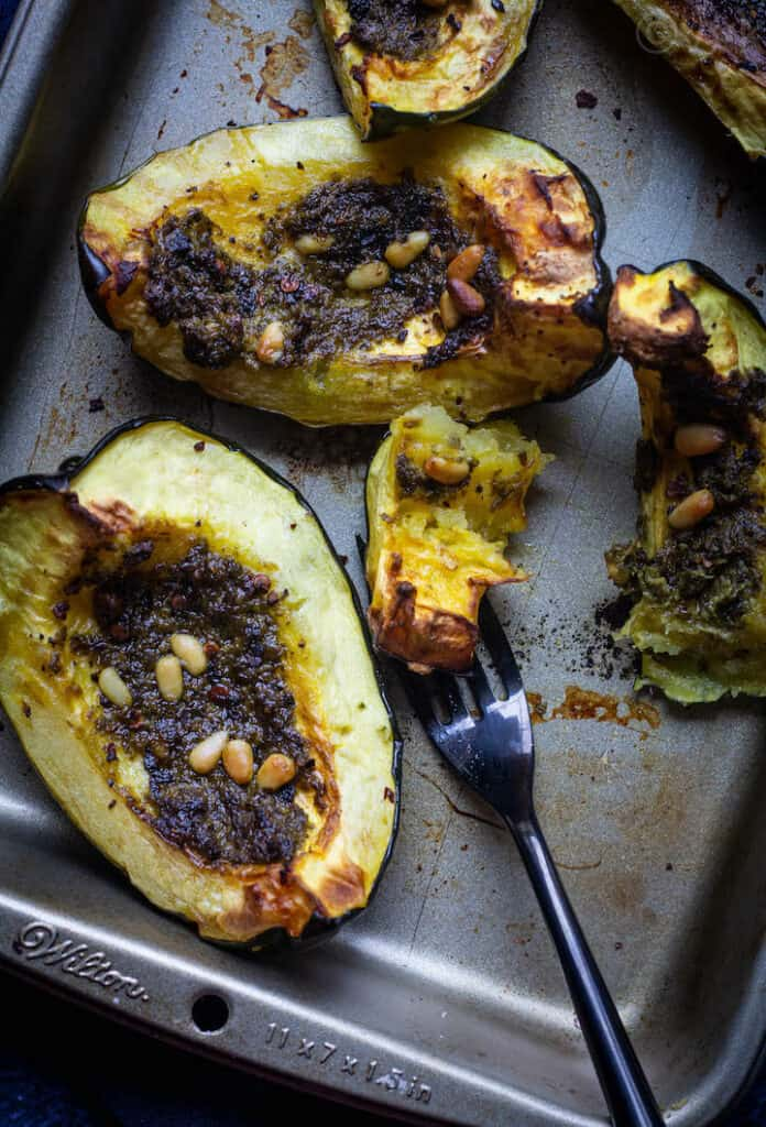 fork-tender acorn squash placed on a baking tray