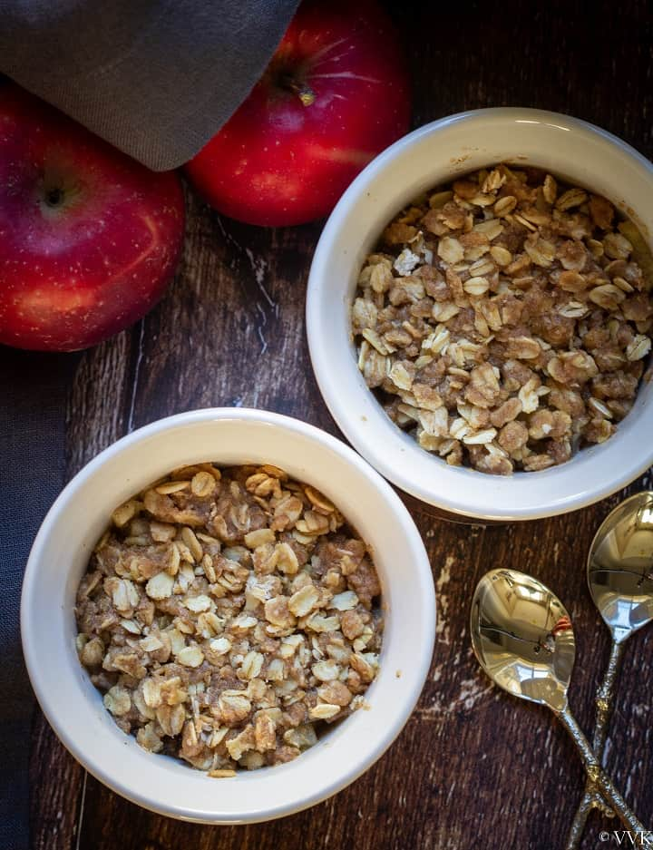 microwave apple crisp served in two ramekins with apples on the side