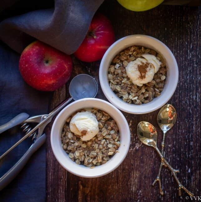 square image of apple crisp served with ice cream in a ceramic bowls
