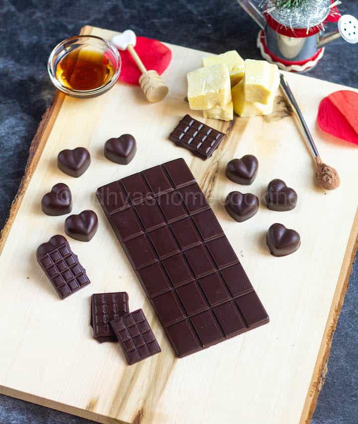 homemade dark chocolate bar and heart shaped ones placed on wooden board