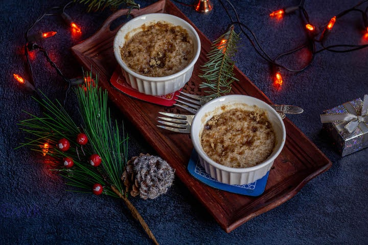 eggless coffee cake served in two ramekins placed on a wooden plate with lights and xmas leaves on the side