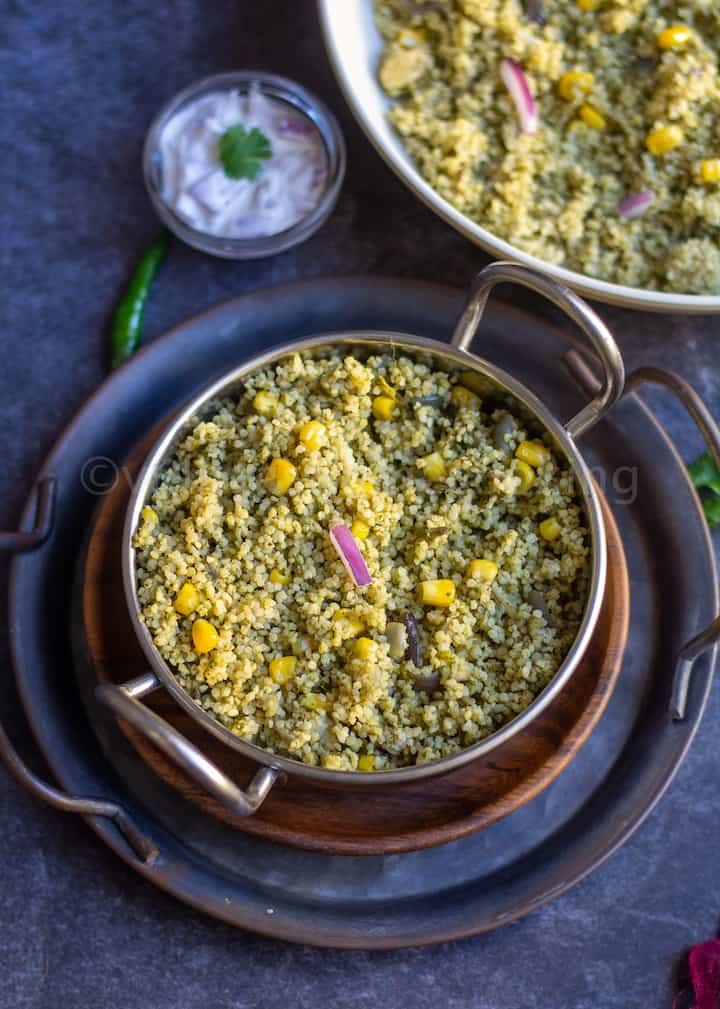 instant pot millet palak pulao served in kadai bowl stacked on trays with raita on the side