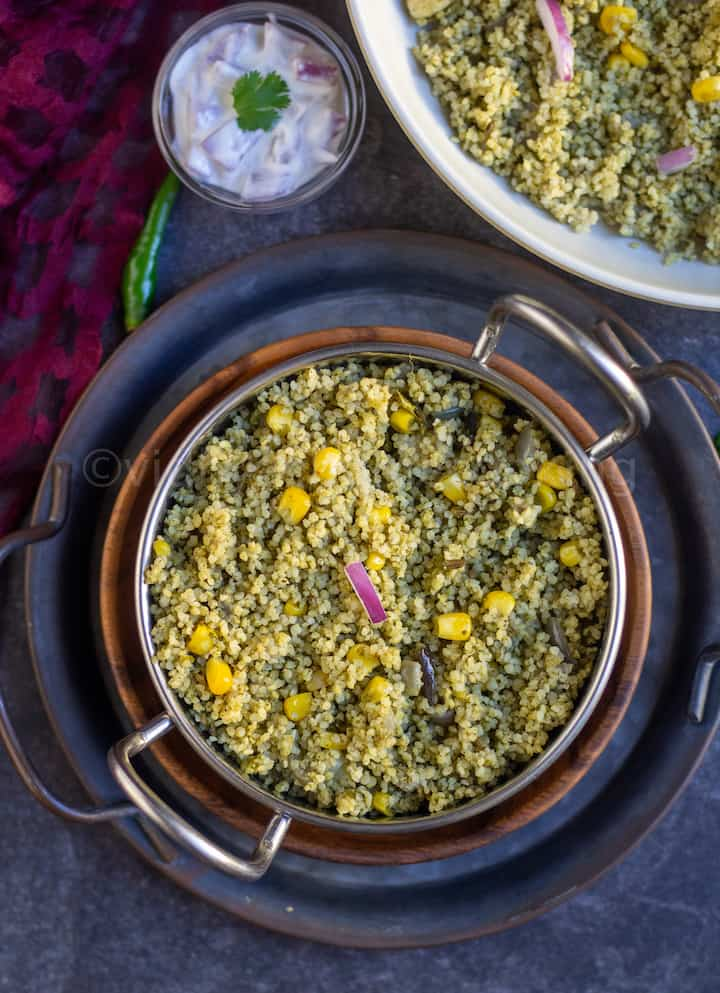 overhead shot of spinach rice served in a kadai stacked on plates with raita on the side