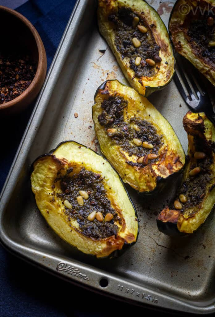 close up shot roasted acorn squash with pesto and pine nuts
