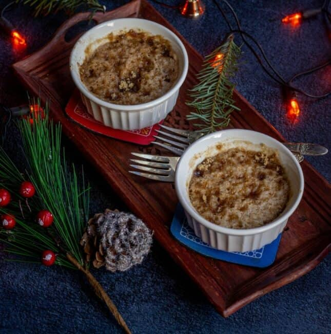 square image of eggless coffee cake served in two ramekins placed on a wooden plate with lights and xmas leaves on the side