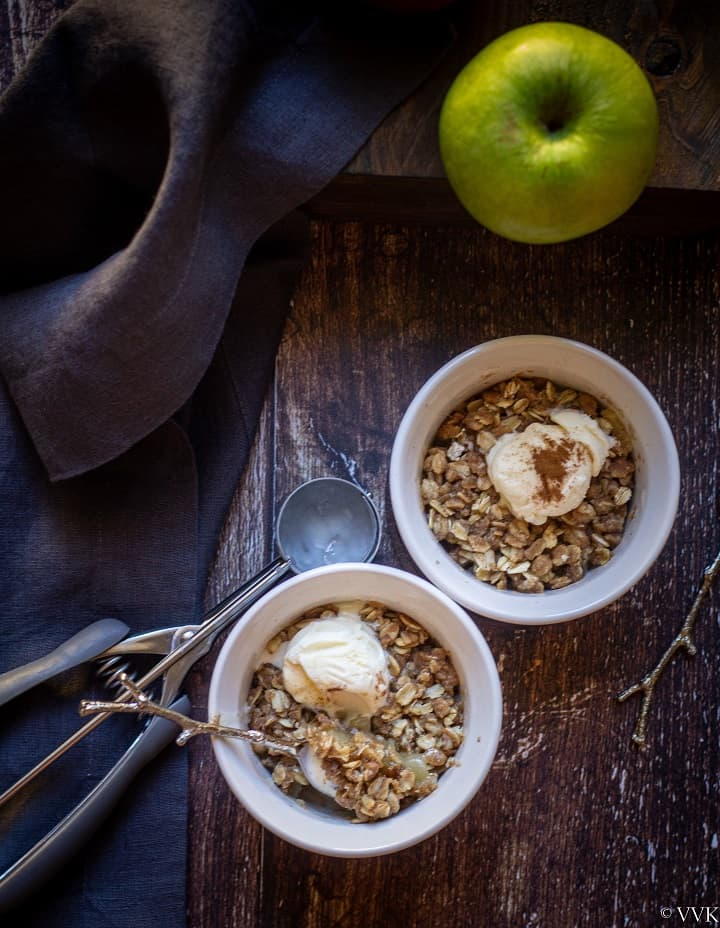 apple crisp served with ice cream in a ceramic bowls topped with icecream