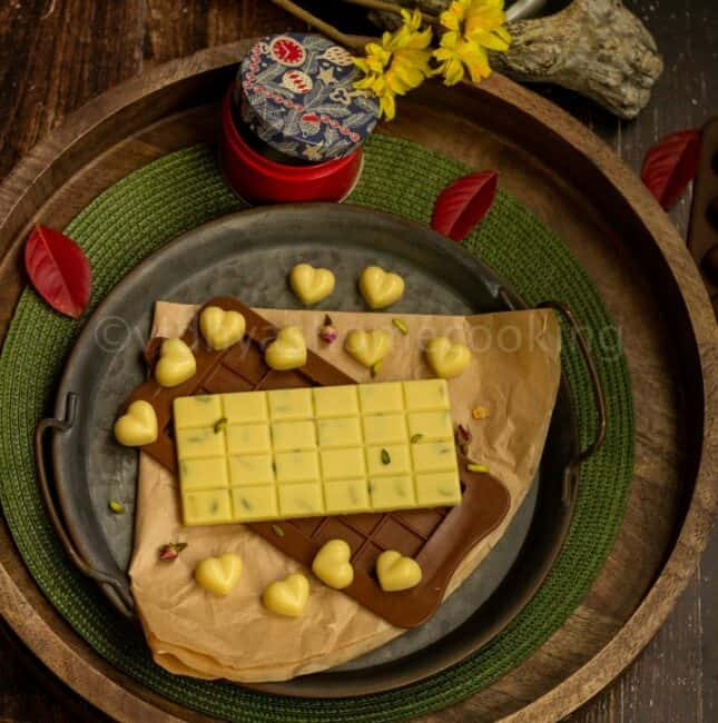 square image of homemade white chocolates layers on a wooden and rustic tray