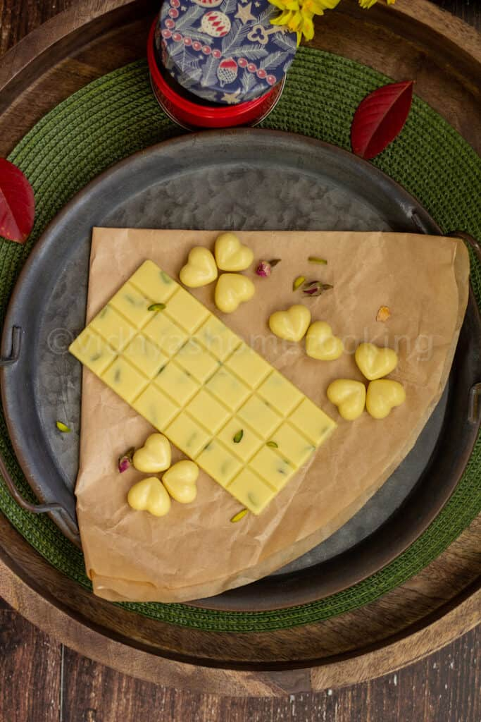 overhead shot of homemade white chocolate bar and heart shaped chocolates placed on a brown paper