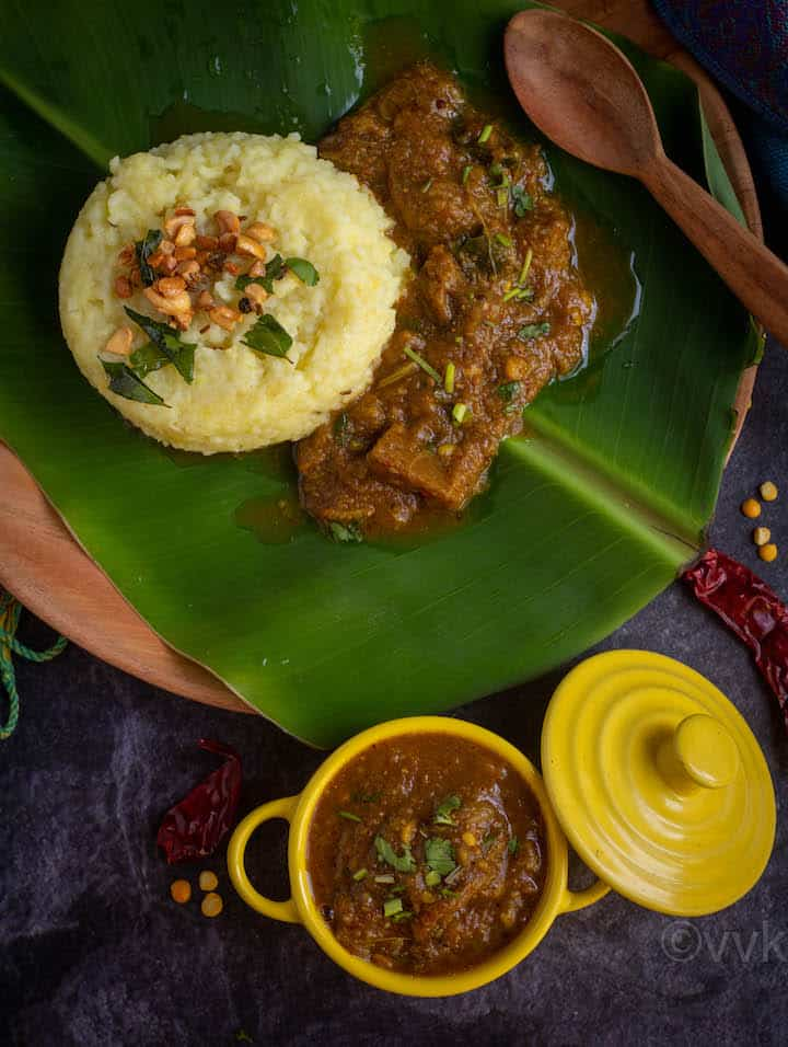 brinjal gothsu served in yellow casserole and plate of pongal and gothsu on the back