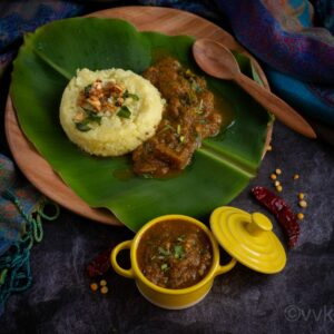square image of brinjal gothsu served in yellow casserole and plate of pongal and gothsu on the back