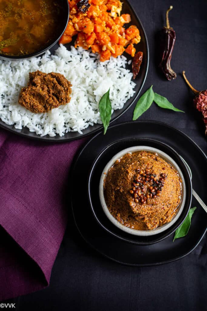 ginger chutney served in white bowl with a plate of rice, rasam and carrot stirfry