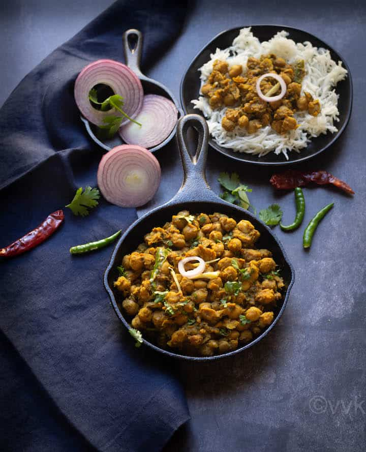 pindi chole served in cast iron skillet with onions and rice on the side