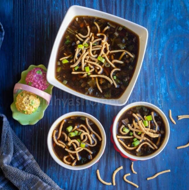 square image of veg manchow soup topped with fried noodles