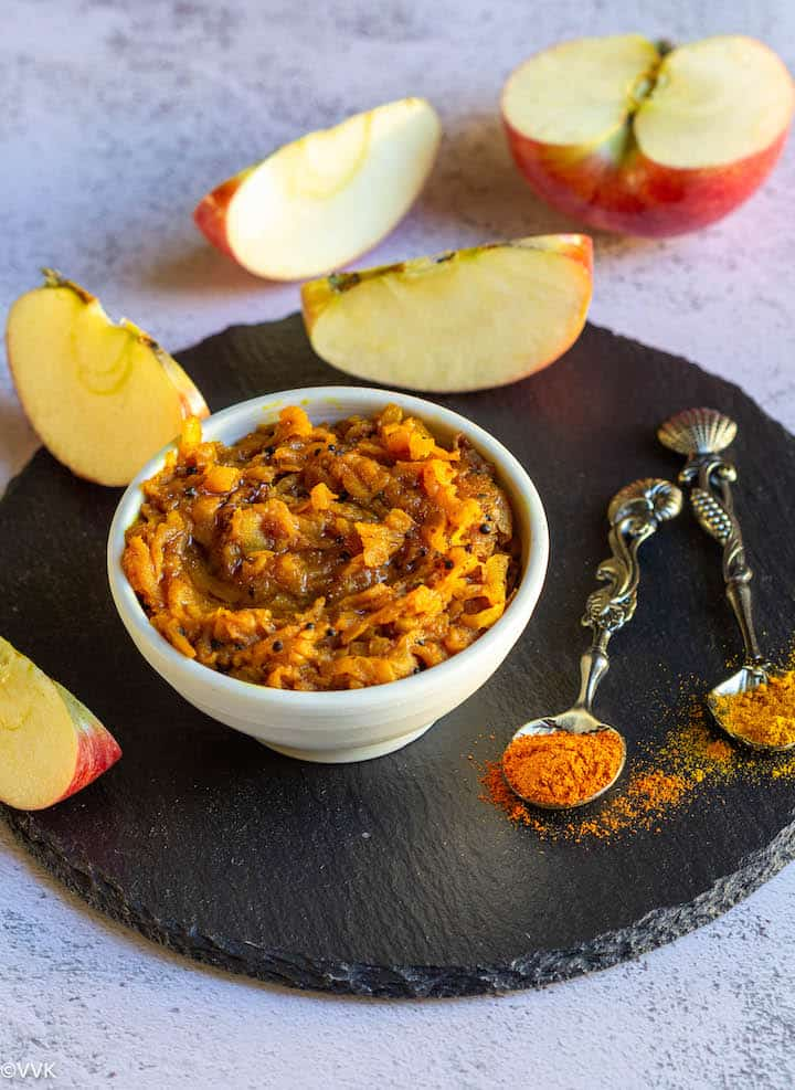 overhead shot of apple pickle with apple slices on the side and with some red chili and turmeric powder sprinkled placed on a slate board