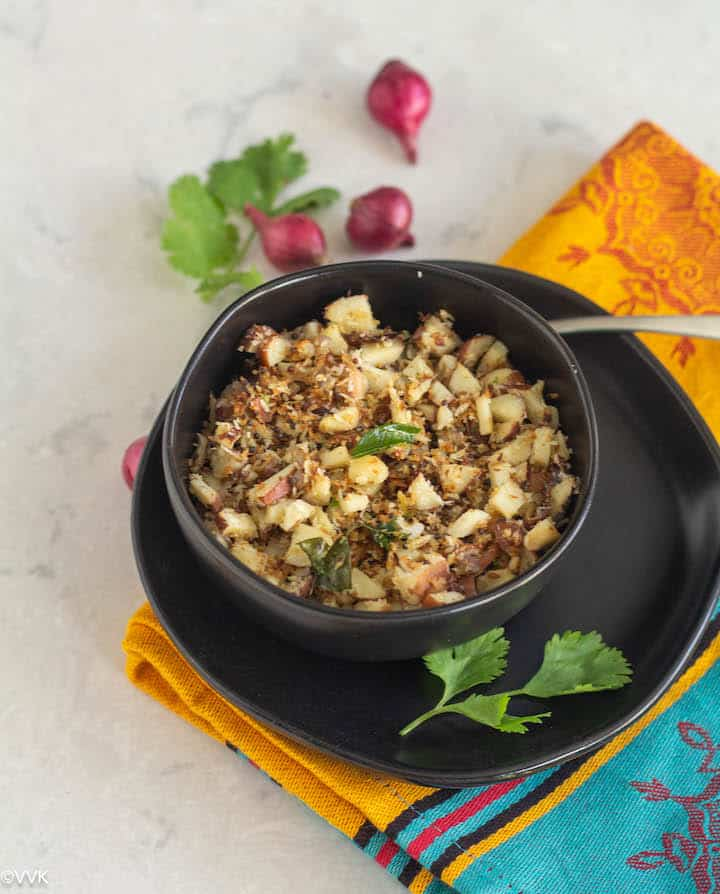 Chakkakuru thoran placed in black bowl on top of a plate with shallots on the top and cilantro in the side