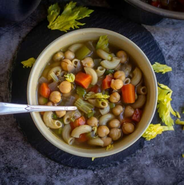 Vegan chickpeas and pasta soup served in ceramic bowl with spoon inside placed on a black slate with celery leaves as garnish