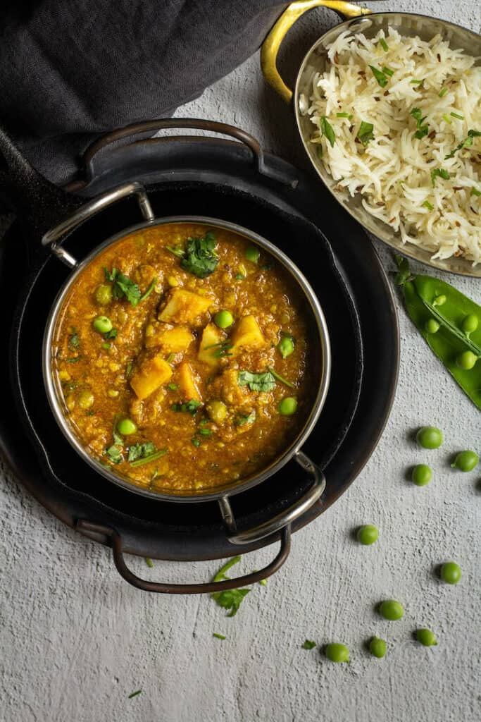matar nimona served in a kadai bowl stacked up on trays with rice on the side and green peas on the other side