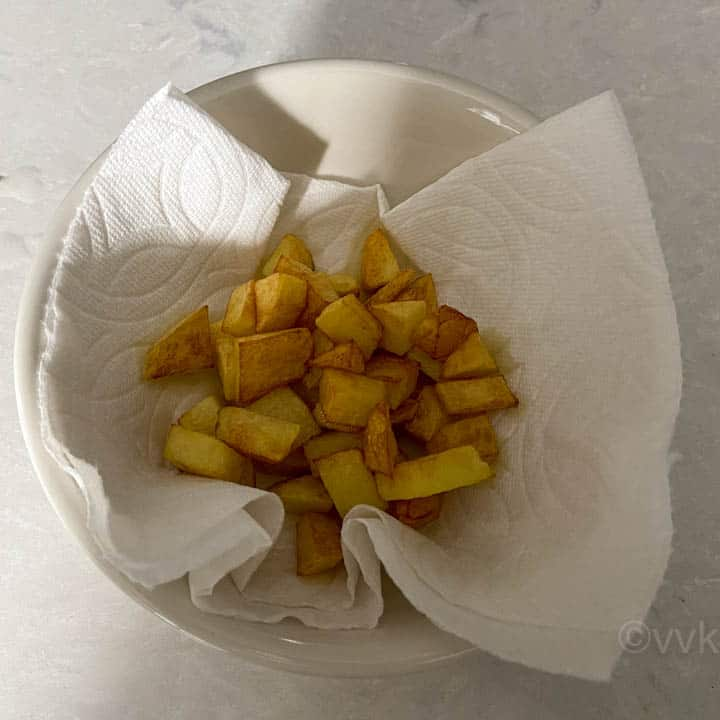 fried potatoes placed on a kitchen towel for draining
