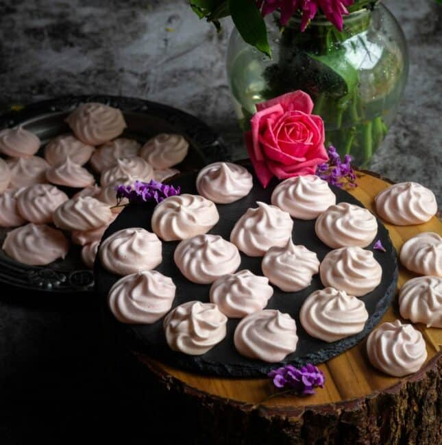 square image of vegan meringue cookies placed on a wooden stand with a flower vase behind