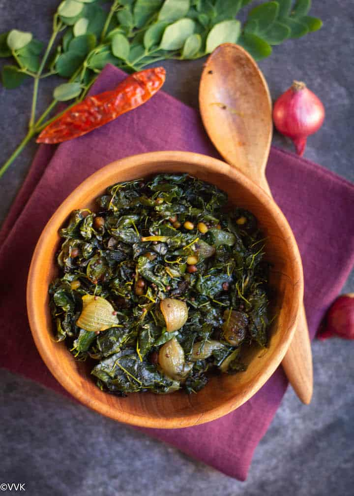moringa leaves stirfry served in neem wood bowl placed on maroon towel
