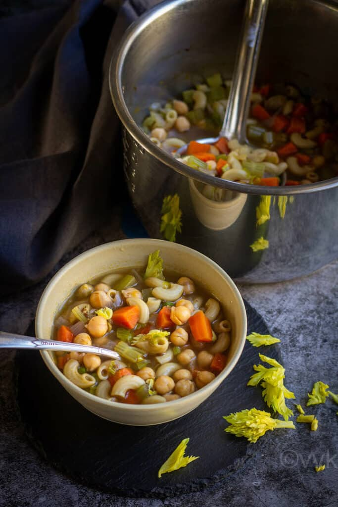 cajun chickpeas soup served in white bowl with instant pot placed behind wrapped with gray fabric