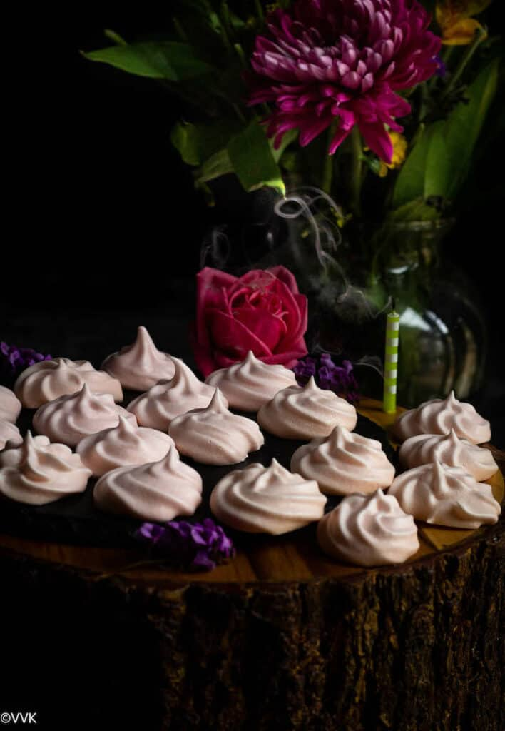 meringue cookies placed on a wooden stand with a flower vase behind