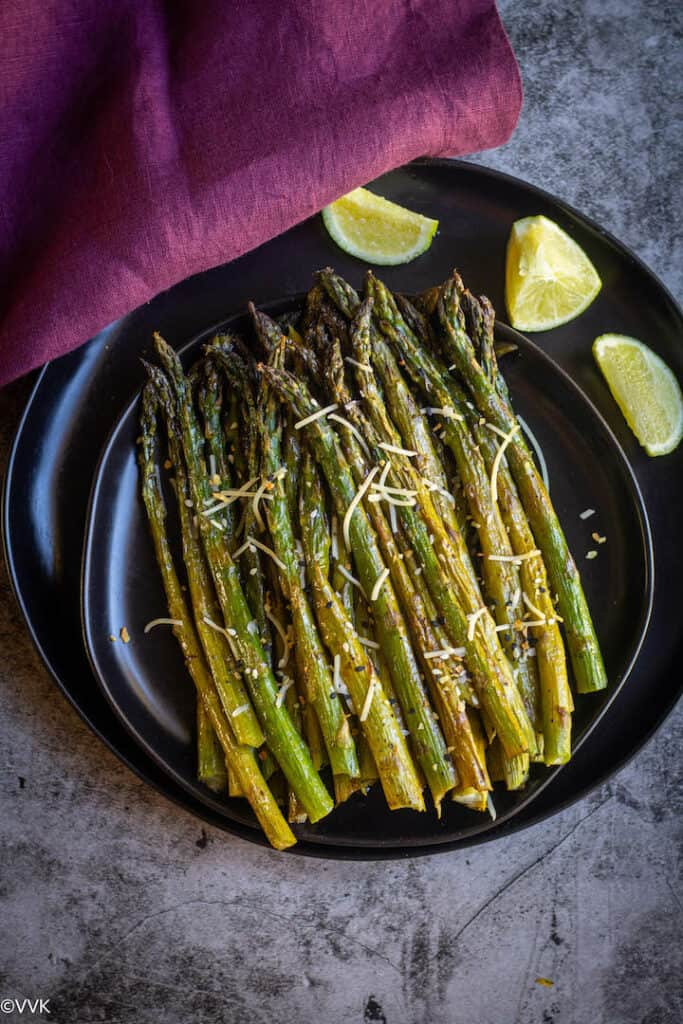 balsamic baked asparagus served on a black plate with a fork on the side and some lemon wedges