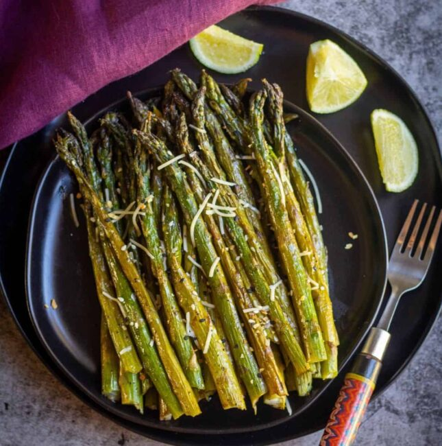 square image of baked asparagus served on a black plate with a fork on the side and some lemon wedges