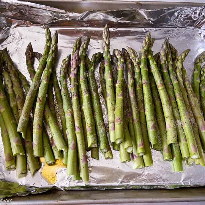 mixing oil, salt, pepper and asparagus