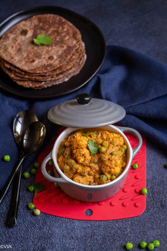 gobi matar served in a gray casserole placed on a red coaster with ragi rotis on the top