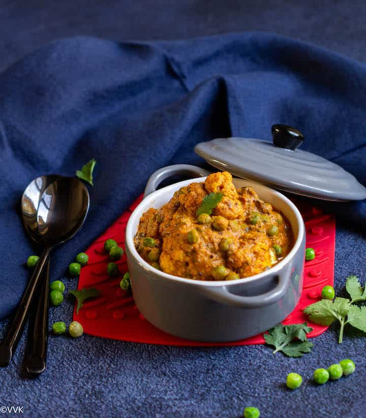 gobi matar served in a gray casserole placed on a red coaster