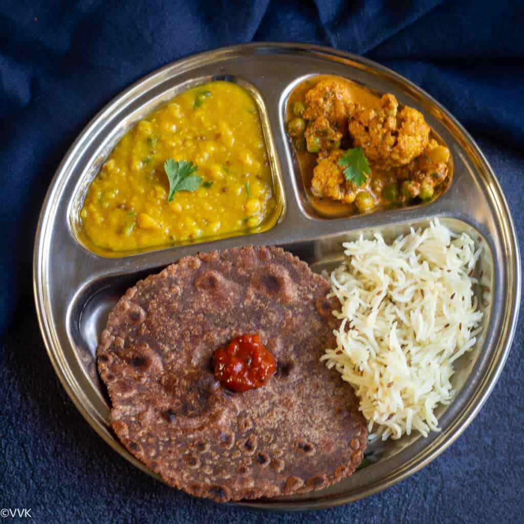 simple indian thali served on a partioned plate with four dishes - dal, rice, curry and roti