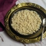 square image of barnyard millet placed in black plate on top of golden plate with purple fabric on the side