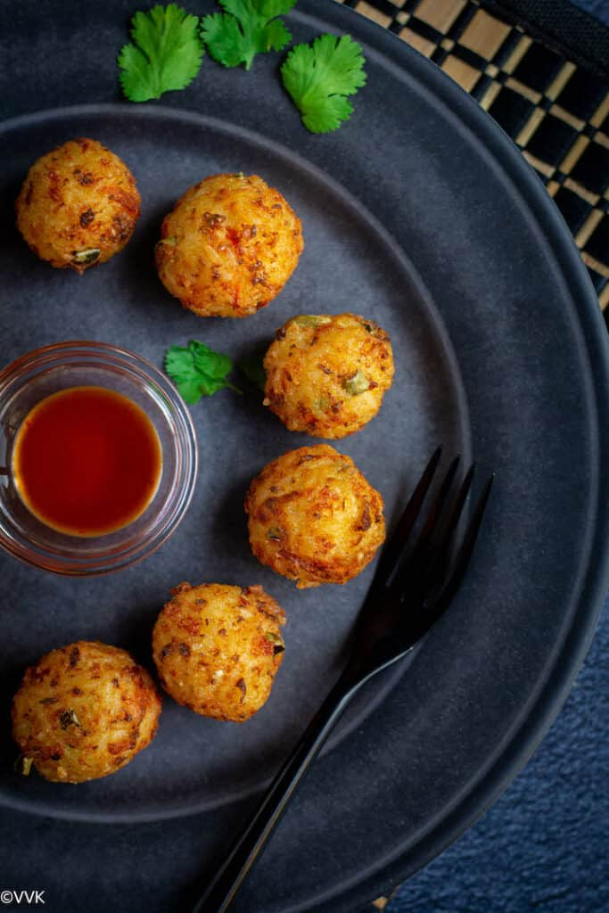 overhead shot of rice veggie and cheese balls served in a blue tray with tomato sauce in the middle