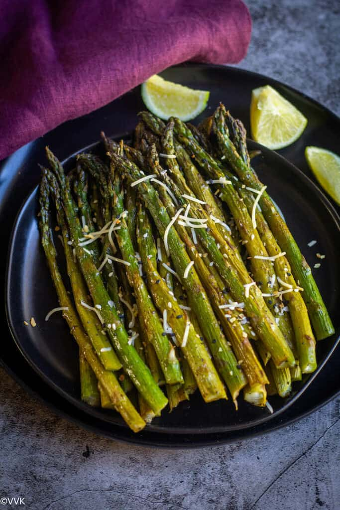 baked asparagus served on a black plate with a fork on the side and some lemon wedges