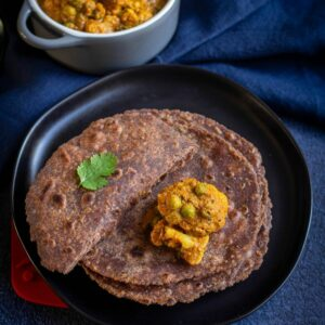 square image of ragi roti served on a black plate with cauliflower curry on top