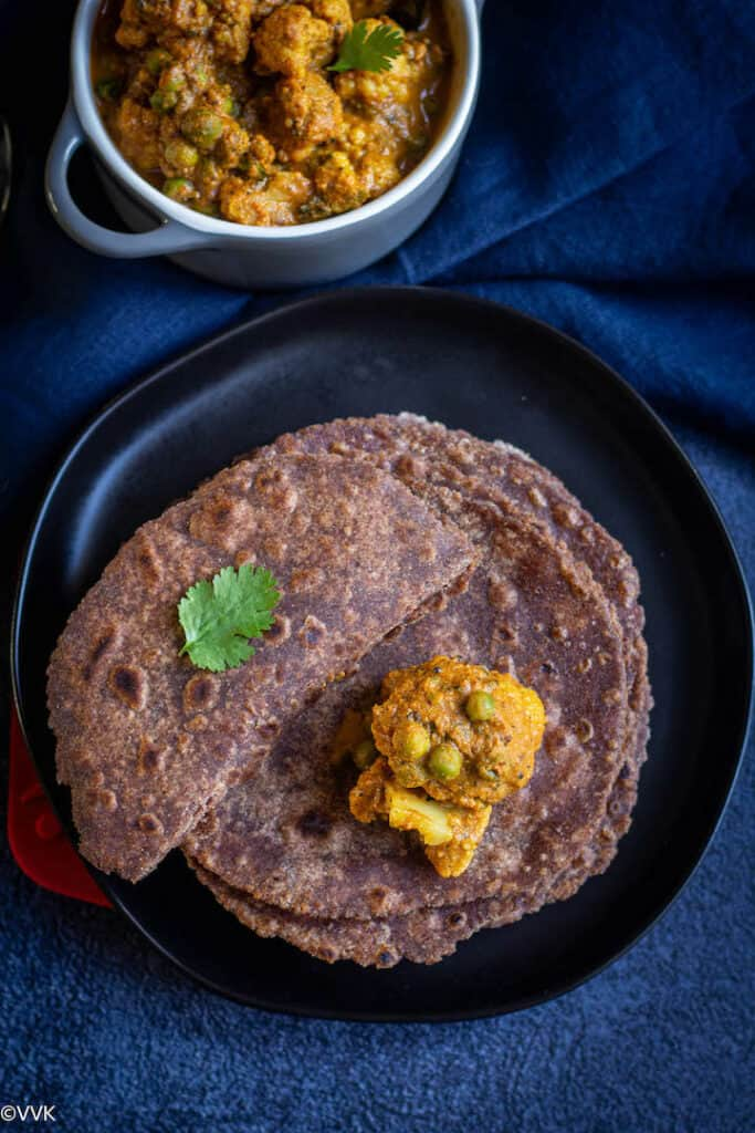stacked up rotis served in a black plate with one roti folded into half and with cauliflower curry on the top