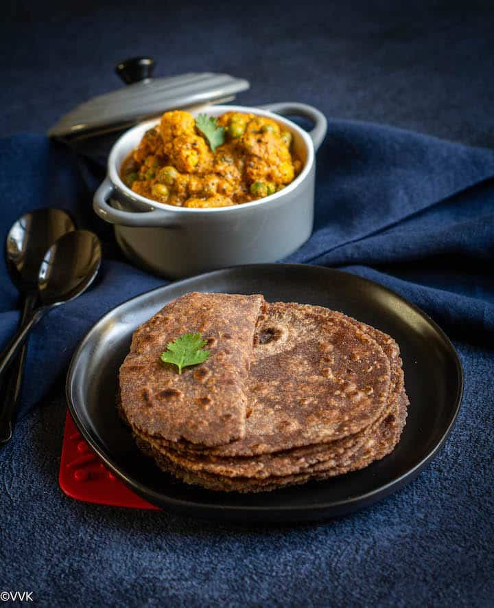 stacked up rotis served in a black plate with one roti folded into half and with cauliflower curry on the side