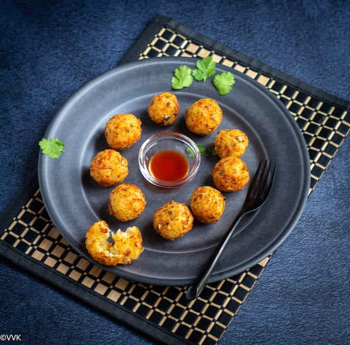 deep fried rice veggie and cheese balls served with tomato sauce in a plate with fork