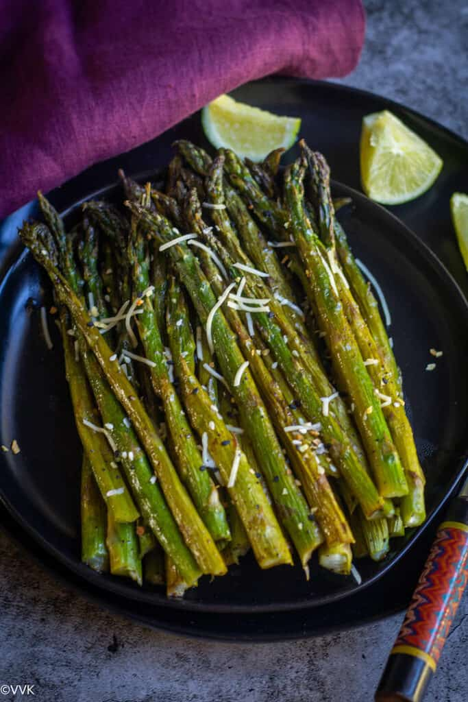 overhead shot of oven-roasted asparagus served on a black plate with lemon wedges on the side