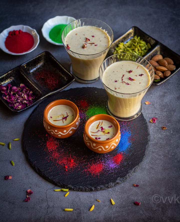 thandai served in kulhad cups and glass cup placed on a black board with colors and with some nuts, saffron and rose petals on the side
