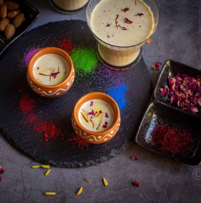 square image of thandai served in kulhad cups and glass cup placed on a black board with colors