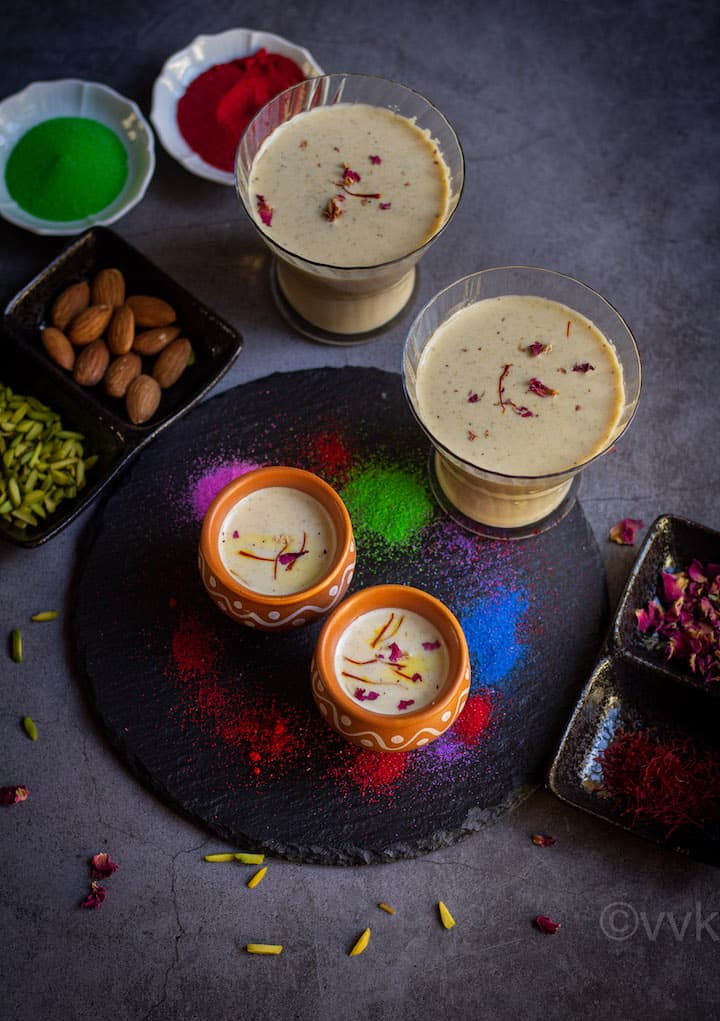 thandai served in kulhad cups and glass cup placed on a black board with colors