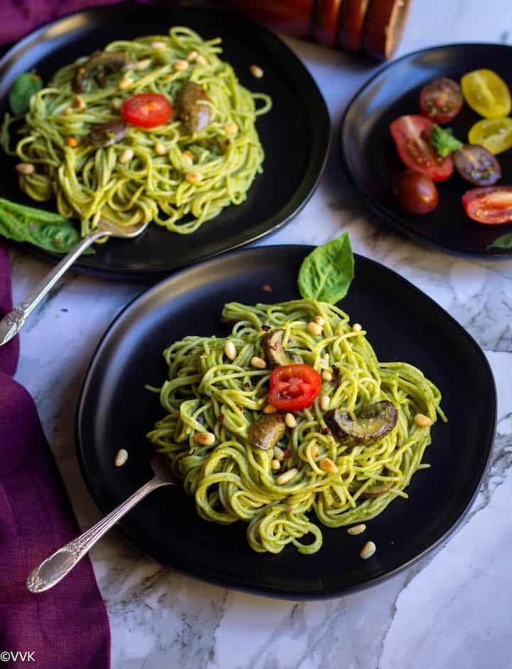 basil pesto pasta with mushrooms served in two black plates