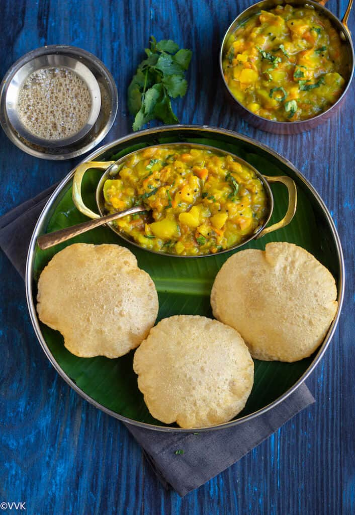 puri served with potato masala in a plate lined with banana leaf and coffee on the side